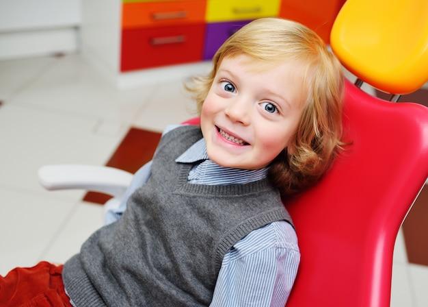 Porträt eines lächelnden kindes mit dem blonden gelockten haar auf prüfung in einem zahnmedizinischen stuhl.