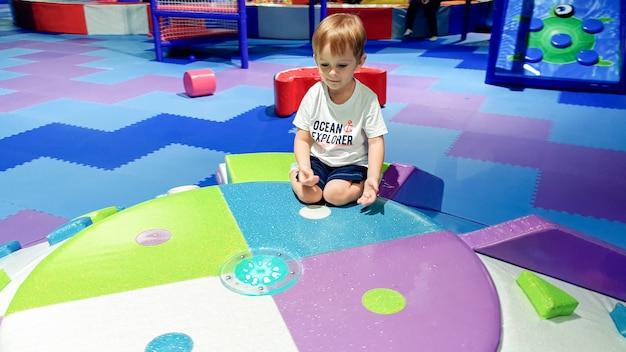 Porträt eines lächelnden kleinen jungen, der auf dem bunten kinderspielplatz im einkaufszentrum sitzt?