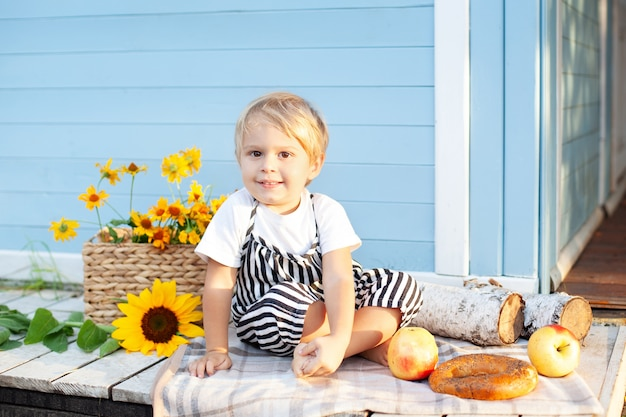 Porträt eines lächelnden kleinen jungen, der auf einer hölzernen veranda zu hause an einem herbsttag sitzt. kindheitskonzept. im herbst spielt ein kind auf dem hof. glückliches kind. ernte. kleiner bauer. charmantes baby