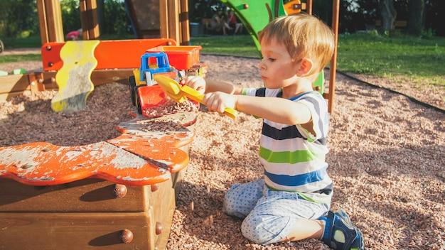 Porträt eines lächelnden kleinen jungen, der im sandkasten auf dem spielplatz sitzt und sand mit plastikspaten gräbt und ihn in bunten spielzeug-lkw mit anhänger gießt