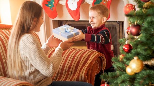 Porträt eines lächelnden kleinen jungen, der seiner mutter, die im großen sessel im wohnzimmer sitzt, eine weihnachtsgeschenkbox gibt