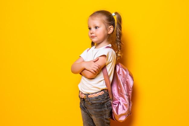 Porträt eines lächelnden kleinen schulmädchens mit rucksack auf gelber wand