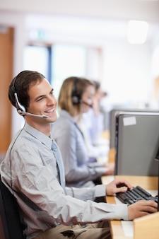 Porträt eines lächelnden kundenassistenten, der einen kopfhörer verwendet