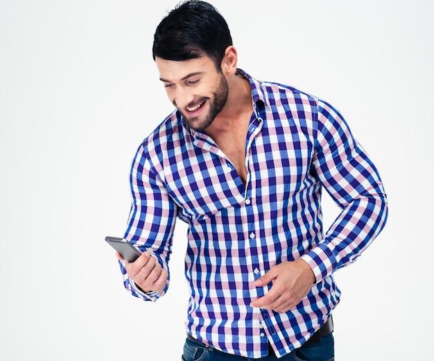 Porträt eines lächelnden lässigen mannes unter verwendung des smartphones lokalisiert auf einer weißen wand
