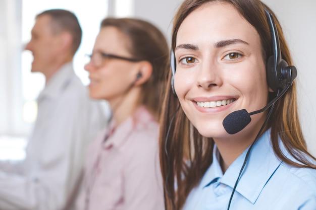 Porträt eines lächelnden mädchen-call-center-betreibers. freundlicher agent der jungen frau