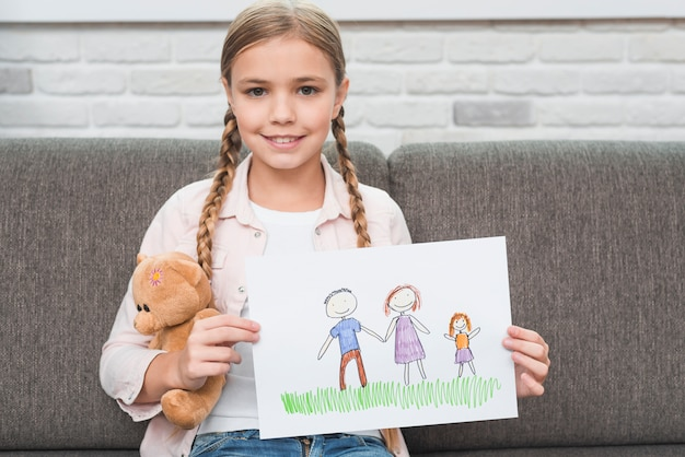 Porträt eines lächelnden mädchens, das auf dem sofa zeigt ihre familienzeichnung auf papier sitzt