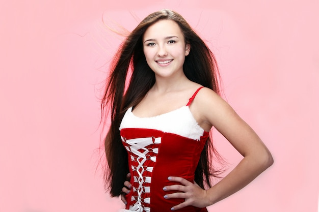 Porträt eines lächelnden mädchens, das ein rotes weihnachtskleid trägt