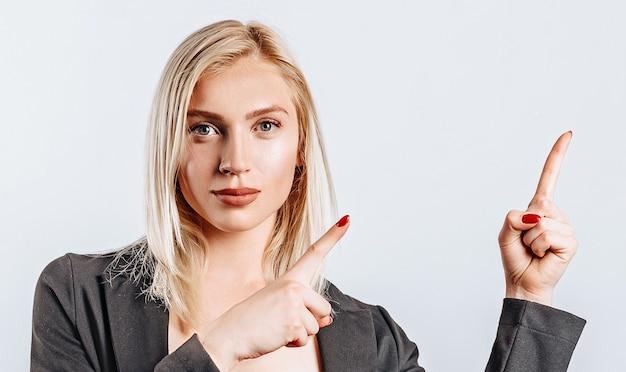 Porträt eines lächelnden mädchens, das finger oben auf copyspace lokalisiert auf einem weißen hintergrund zeigt. eine frau zeigt auf eine idee, einen ort für werbung. positive blondine.