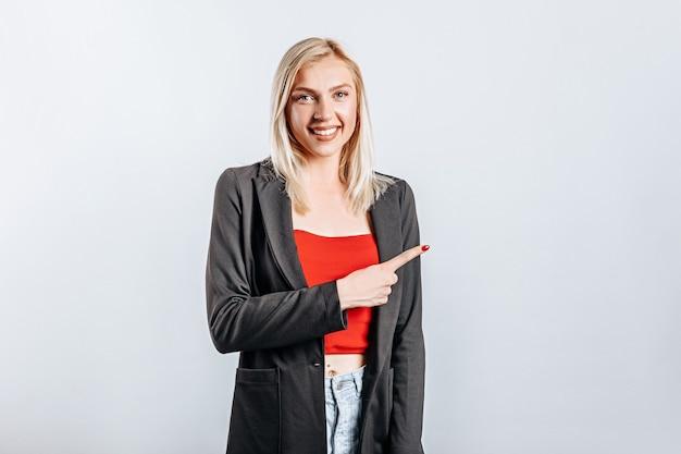 Porträt eines lächelnden mädchens, das finger oben auf kopienraum zeigt. eine frau zeigt auf eine idee, einen ort für werbung. positive blondine.