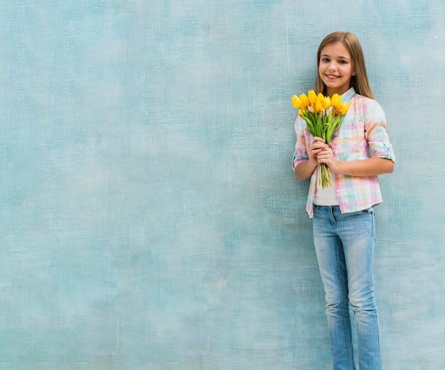 Porträt eines lächelnden mädchens, das gelbe tulpe hält, blüht in der hand, die gegen blaue wand steht