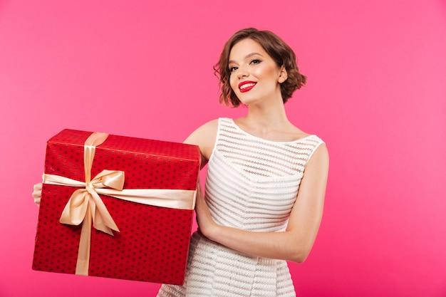 Porträt eines lächelnden mädchens kleidete im kleid an, das geschenkbox hält