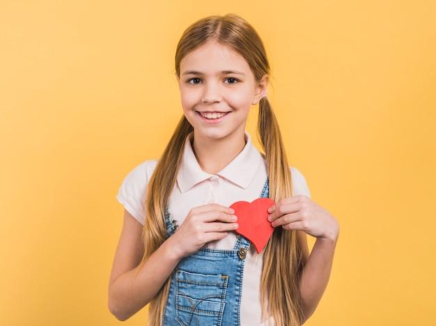 Porträt eines lächelnden mädchens mit dem blonden langen haar, das rotes papier zeigt, schnitt das herz heraus, das gegen gelben hintergrund steht