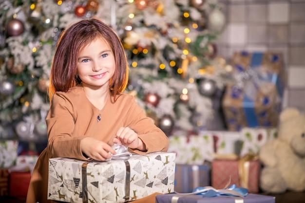 Porträt eines lächelnden mädchens mit einer großen schachtel mit einem geschenk gegen den weihnachtsbaum