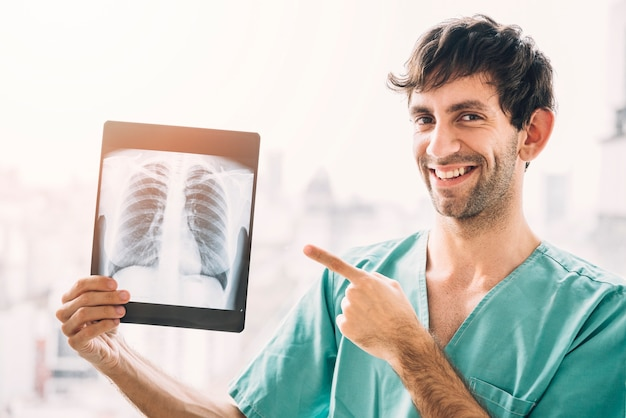Porträt eines lächelnden männlichen doktors, der kastenröntgenstrahl zeigt