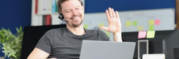 Porträt eines lächelnden männlichen operators, der den kunden per videoanruf begrüßt, fernarbeit durch den operator