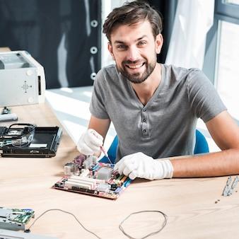 Porträt eines lächelnden männlichen technikers, der computermotherboard repariert