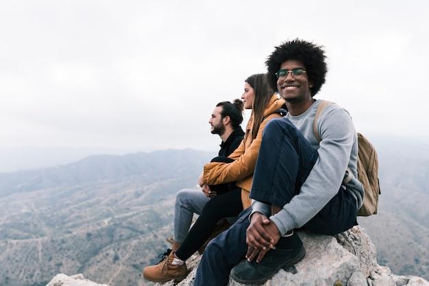 Porträt eines lächelnden mannes, der auf die oberseite des felsens genießt mit seinem freund sitzt
