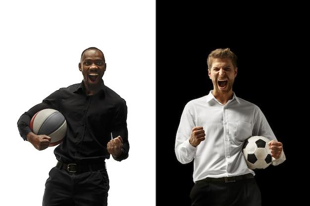 Porträt eines lächelnden mannes, der fußball und basketballball lokalisiert auf einem weißen und schwarzen hintergrund hält. der erfolg glücklich afro und kaukasische männer. gemischtes paar.