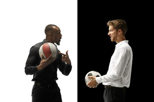 Porträt eines lächelnden mannes, der fußball und basketballball lokalisiert auf einem weißen und schwarzen raum hält