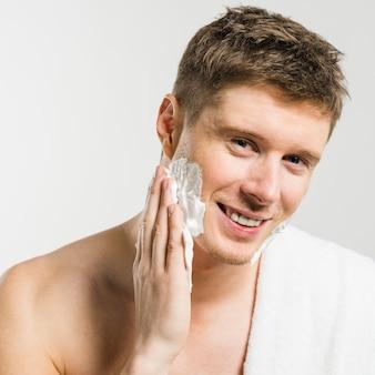 Porträt eines lächelnden mannes, der schaum auf seinem gesicht mit der hand gegen weißen hintergrund rasierend zutrifft