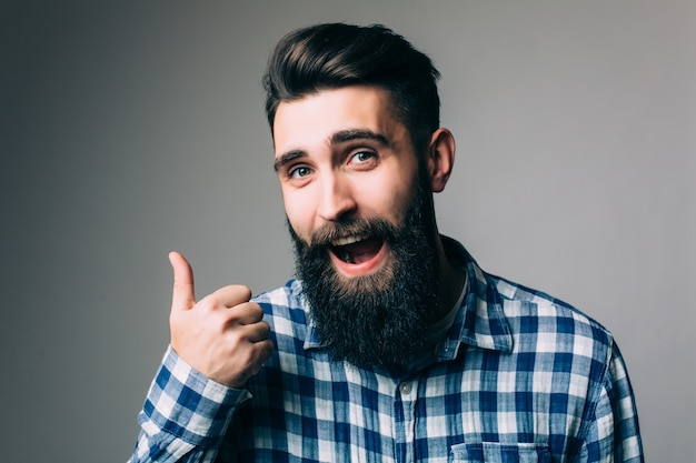 Porträt eines lächelnden mannes in der brille, die daumen oben über graue wand zeigt