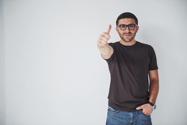 Porträt eines lächelnden mannes in der brille, die daumen oben über weiß zeigt