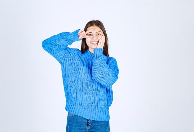 Porträt eines lächelnden modells des jungen mädchens, das victory-zeichen nahe auge zeigt.