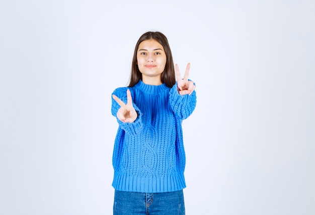 Porträt eines lächelnden modells des jungen mädchens, das victory-zeichen zeigt.