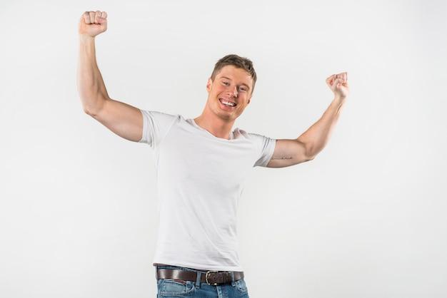 Porträt eines lächelnden muskulösen mannes, der ihre faust gegen weißen hintergrund zusammenpreßt