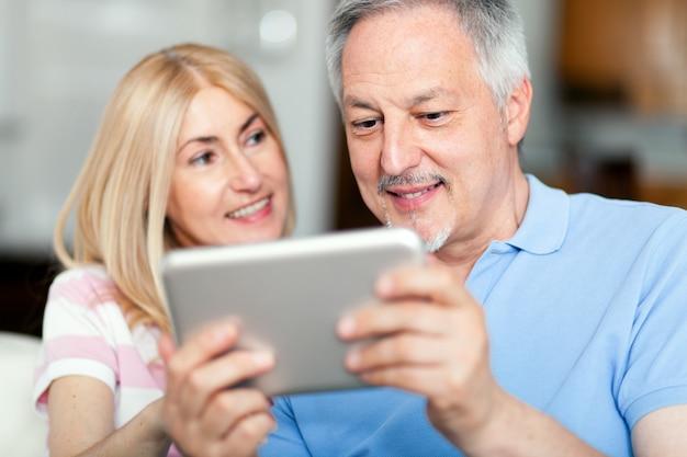 Porträt eines lächelnden reifen paares, das digitales tablett auf sofa zu hause verwendet