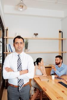 Porträt eines lächelnden, selbstbewussten indischen unternehmers mit verschränkten armen und blick in die kamera, seine kollegen sprechen am tisch im besprechungsraum