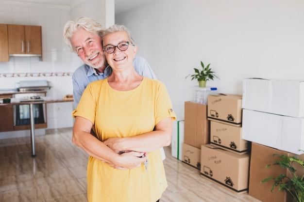 Porträt eines lächelnden seniorenpaares mit weißem haar, das während des umzugs umarmt wurde, glücklich für den neuanfang wie im ruhestand mit umzugskartons auf dem boden