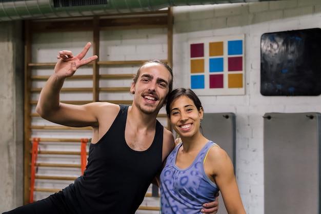 Porträt eines lächelnden sportlichen paares im fitnessstudio