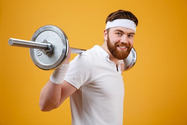 Porträt eines lächelnden sportmannes, der übungen mit langhantel macht