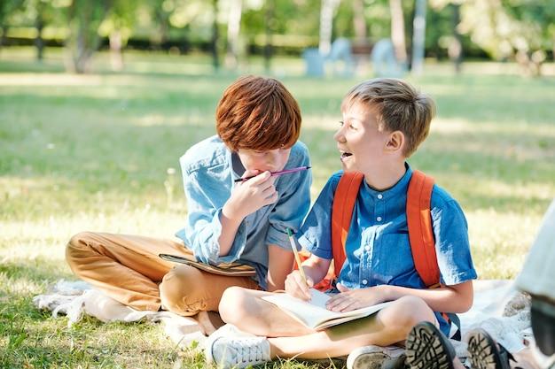 Porträt eines lächelnden teenager-mädchens, das zu seinem klassenkameraden schaut, während er den unterricht im freien im sonnenlicht mit einem männlichen lehrer genießt