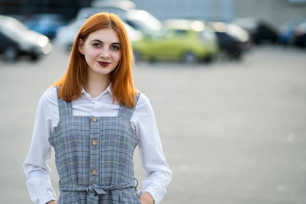 Porträt eines lächelnden teenager-mädchens mit roten haaren und klaren augen, die modisches lässiges kleid tragen, das draußen im warmen sommertag steht.