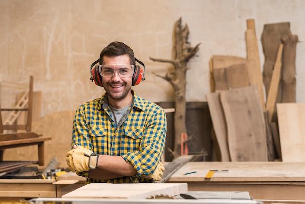 Porträt eines lächelnden tragenden sicherheitsglases und des ohrenschützers des tischlers in der werkstatt