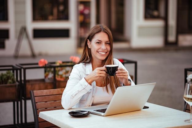 Porträt eines lächelnden trinkbechers der jungen frau beim sitzen vor laptop im café.