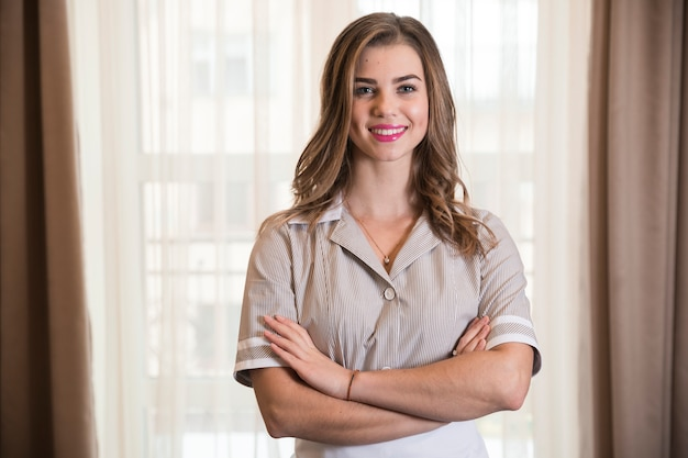 Porträt eines lächelnden überzeugten jungen stubenmädchens im hotelzimmer