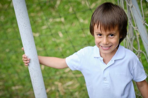 Porträt eines lächelnden und glücklichen kindergesichtes, das die kamera beim halten mit einem arm einer röhre betrachtet.
