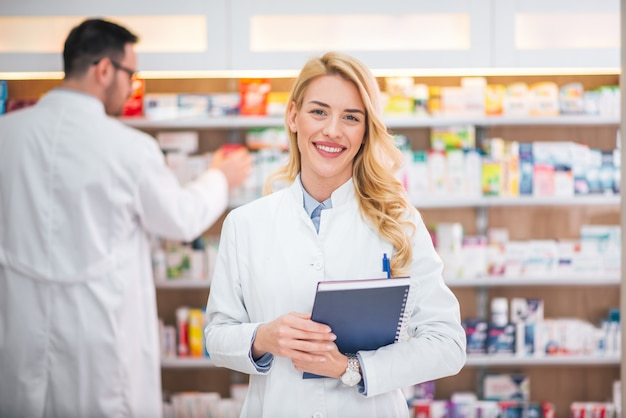 Porträt eines lächelnden weiblichen apothekers, männlicher kollege, der mit drogen arbeitet