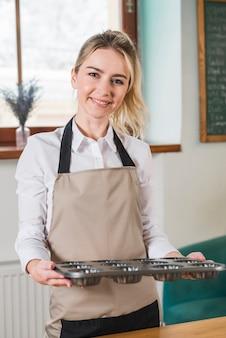 Porträt eines lächelnden weiblichen bäckers, der gebackene muffinsformen hält