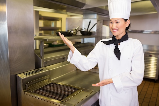 Porträt eines lächelnden weiblichen kochs in der küche