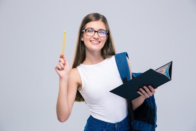 Porträt eines lächelnden weiblichen teenagers, der buch und bleistift isoliert hält