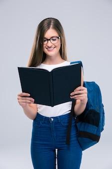 Porträt eines lächelnden weiblichen teenagers mit rucksacklesebuch isoliert