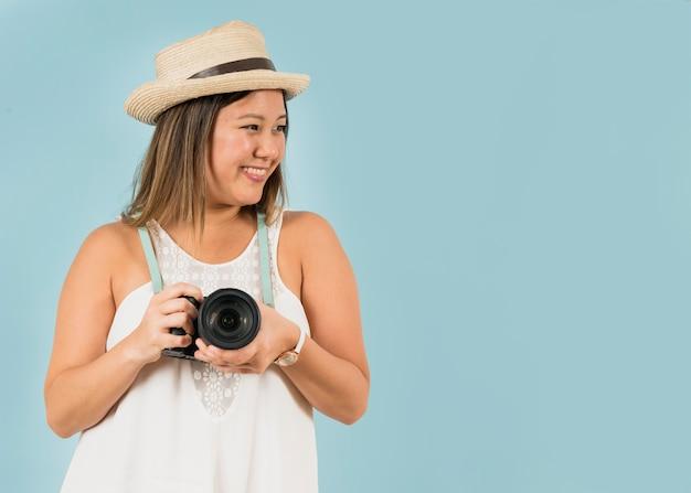 Porträt eines lächelnden weiblichen touristen, der kamera um ihren hals gegen blauen hintergrund hält
