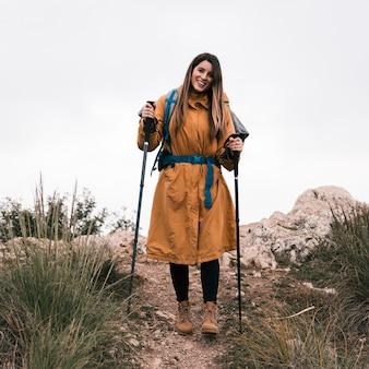 Porträt eines lächelnden weiblichen wanderers, der den wanderstock betrachtet kamera hält