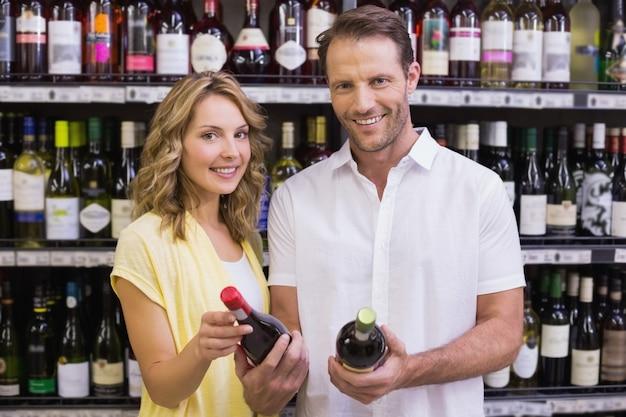 Porträt eines lächelnden zufälligen paares, das weinflasche betrachtet