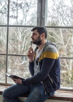 Porträt eines lässigen bärtigen hipster-mannes, der den stift hält und sich notizen im schreibheft macht