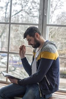 Porträt eines lässigen bärtigen hipster-mannes, der zu hause im schreibheft oder notizblock nachdenkt und notizen macht